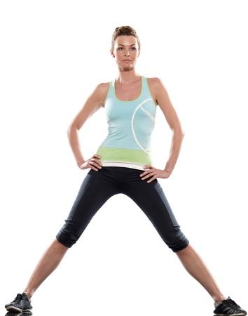 ropa deportiva: se extiende la postura de entrenamiento por una mujer en el estudio de fondo blanco Foto de archivo