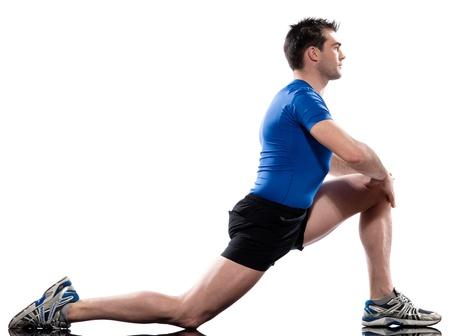 gimnasia aerobica: un hombre cauc�sico Entrenamiento Postura de fitness ejercicio de estiramiento en las piernas de rodillas estudio de fondo blanco Foto de archivo