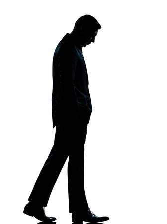 homme triste: une entreprise caucasien homme silhouette marchant sur toute la longueur en studio isol� sur fond blanc