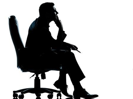 un hombre de negocios caucásico sentado en longitud de la silueta completa sillón en el estudio aislado sobre fondo blanco