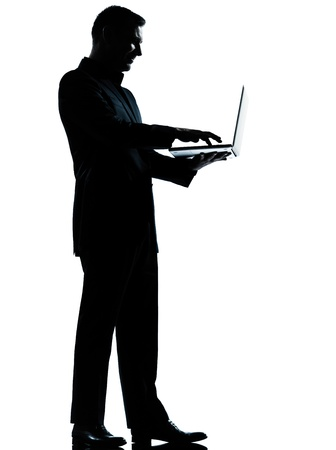 standing: one caucasian business man computing computer laptop silhouette standing Full length in studio isolated on white background