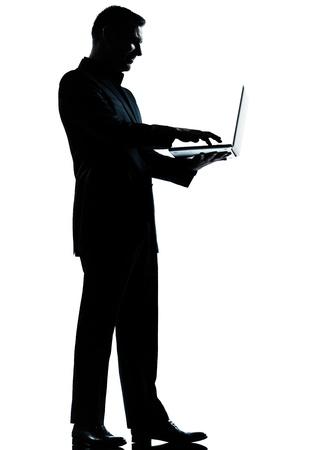 persona de pie: un hombre de negocios cauc�sico equipo de computaci�n port�til silueta de cuerpo entero de pie en el estudio aislado sobre fondo blanco