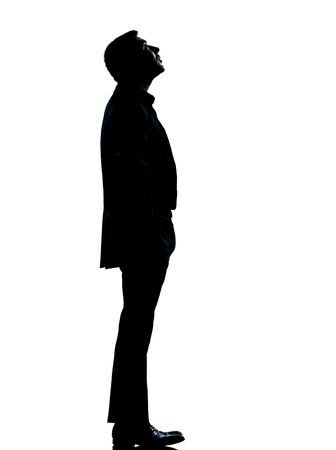 man side view: one caucasian business man silhouette standing looking up Full length in studio isolated on white background