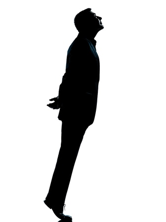 tiptoe: one caucasian business man silhouette standing tiptoe looking up Full length in studio isolated on white background