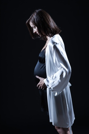 beautiful smiling caucasian pregnant  woman portraitt   touching her belly in nightie on studio isolated black background Stock Photo - 11765083