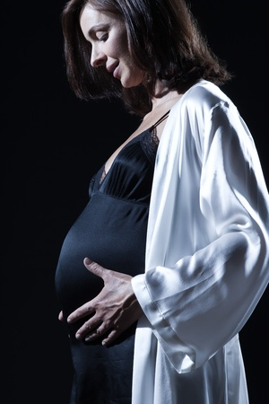 beautiful smiling caucasian pregnant  woman portraitt   touching her belly in nightie on studio isolated black background photo