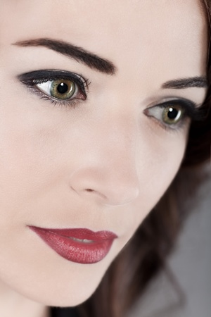 Closeup portrait of a thoughtful beautiful middle aged womans green eyes and red lips photo