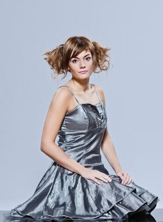 traje de gala: joven y bella mujer caucasian niña de vestido de noche sentados toda su longitud en el suelo en estudio sencillo fondo blanco