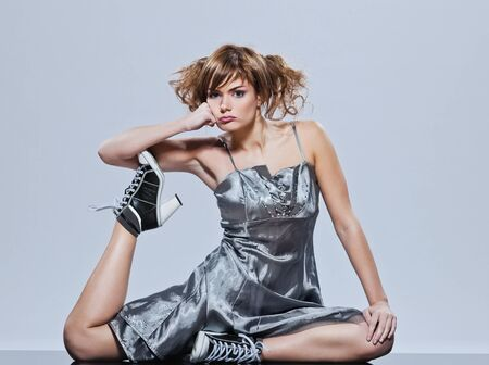 sulk: beautiful young caucasian woman girl evening dress sullen sulk sitting on the floor on studio isolated plain background Stock Photo