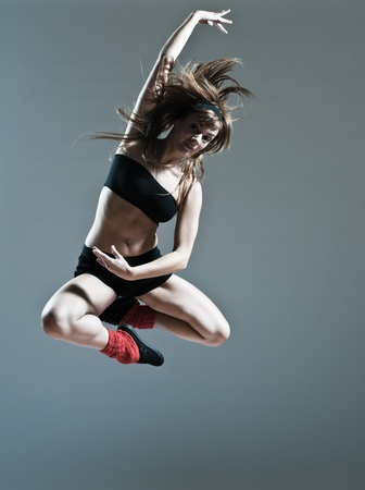 gravity: beautiful young caucasian woman girl dancer ballet breakdance leap jump on studio isolated background