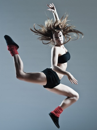 breakdancer: beautiful young caucasian woman girl dancer ballet breakdance leap jump on studio isolated background
