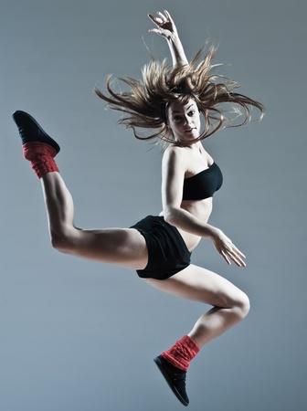 gravedad: joven y bella mujer de raza caucásica mujer bailarina de ballet breakdance salto salto en el fondo estudio aislado Foto de archivo