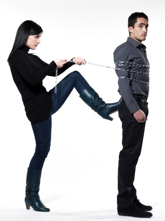 domination: woman binding his man with a chain on white background