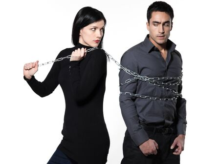 suspicious: woman binding his man with a chain on white background
