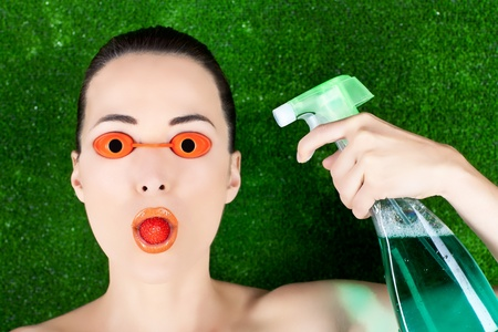 Closeup of a beautiful woman wearing tanning bed glasses with strawberry in mouth and spray bottle in hand against green photo