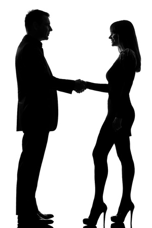 welcoming: one caucasian couple man and woman handshake in studio silhouette isolated on white background