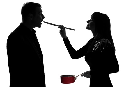 profile: one caucasian couple man and woman tasting cooking sauce pan in studio silhouette isolated on white background Stock Photo