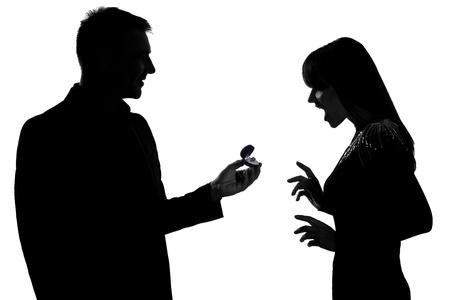 siluetas de enamorados: un hombre caucásico par que ofrece el anillo de compromiso y de la mujer sorprendida en el estudio de silueta aislados sobre fondo blanco