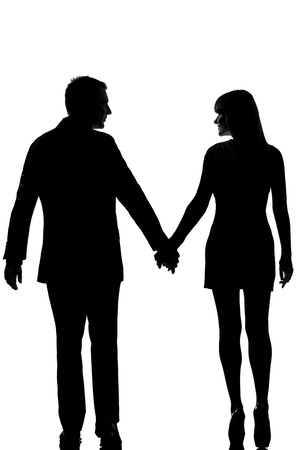 loving hands: rear view one lovers caucasian couple man and woman walking hand in hand in studio silhouette isolated on white background