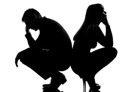 relationship problem: one sad caucasian couple man and woman crouching back to back in studio silhouette isolated on white background