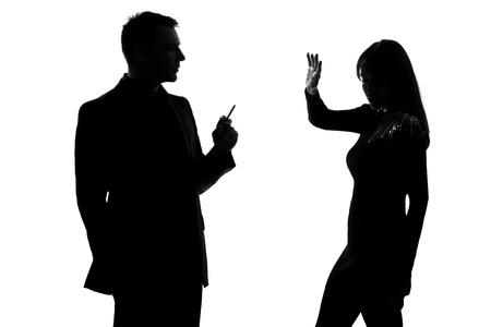 couple lit: one caucasian couple man smoking cigarette and woman disturbed in studio silhouette isolated on white background Stock Photo