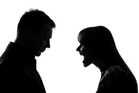 quarrel: one caucasian couple man and woman face to face screaming shouting dipute in studio silhouette isolated on white background Stock Photo