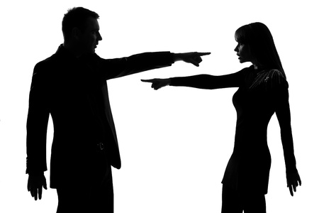 one caucasian couple man and woman pointing at each other expressing accusation in studio silhouette isolated on white background