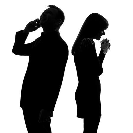 couple lit: una pareja cauc�sica de pie espalda con espalda al hombre en el tel�fono y una mujer llorando en el estudio de silueta aislados sobre fondo blanco
