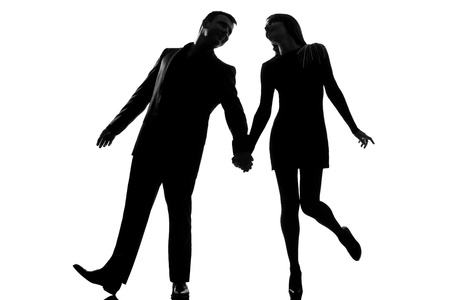 couple lit: one lovers caucasian couple man and woman walking holding hands  in studio silhouette isolated on white background Stock Photo