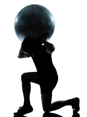 one n man workout holding fitness ball exercising workout aerobic fitness posture full length silouhette on studio isolated on white background photo