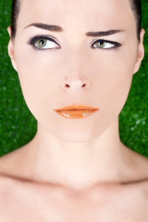Closeup portrait of a beautiful angry woman with glossy lips looking away on green background photo
