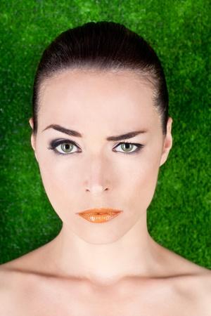 mistrust: Closeup portrait of a serious beautiful woman raising an eyebrow on green background Stock Photo