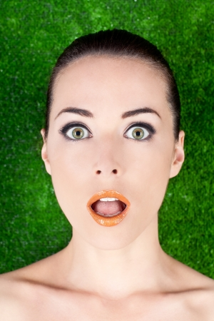 Closeup portrait of a surprised beautiful woman mouth open on green photo