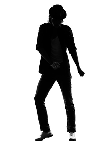 full length silhouette of a young man dancer dancing funky hip hop r&b on  isolated  studio white background photo