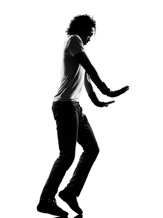full length silhouette of a young man dancer moonwalk dancing funky hip hop r&b on  isolated  studio white background photo