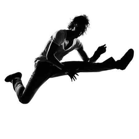 dancer silhouette: full length silhouette of a young man dancer dancing funky hip hop r&b on  isolated  studio white background