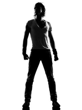 danseres silhouet: volledige lengte silhouet van een jonge man danser dansen staan funky hip hop r & b op geïsoleerde studio witte achtergrond