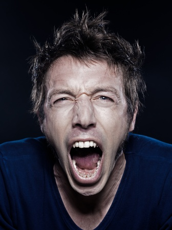 studio portrait on black background of a funny expressive caucasian man screaming photo