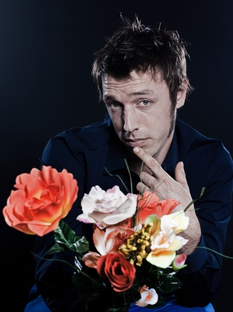 studio portrait on black background of a funny expressive caucasian man offering flowers shy photo