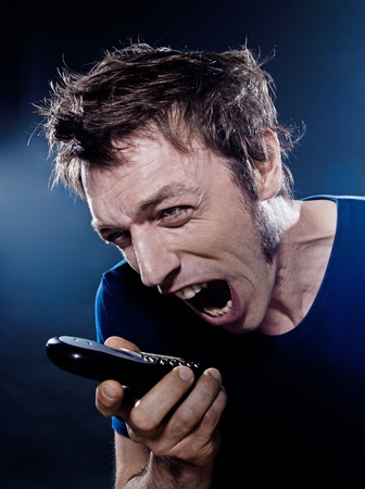 studio portrait on black background of a funny expressive caucasian man yelling at phone photo