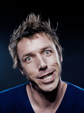 studio portrait on black background of a funny expressive caucasian man grimacing toothy smile photo