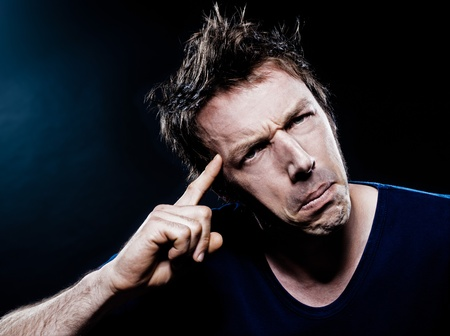 puckering: studio portrait on black background of a funny expressive caucasian man puckering annoyed Stock Photo