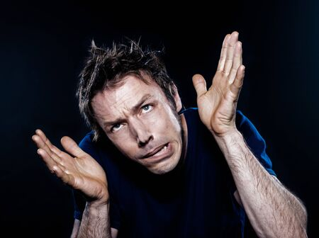 studio portrait on black background of a funny expressive caucasian man puckering scared fear photo