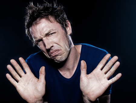 denying: studio portrait on black background of a funny expressive caucasian man frowning refusal deny Stock Photo