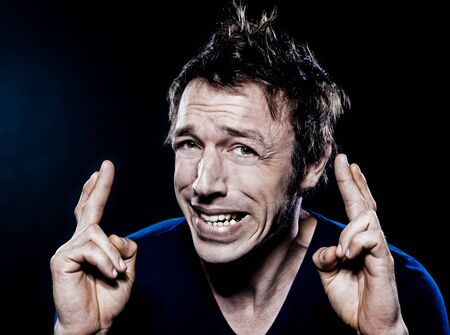 studio portrait on black background of a funny expressive caucasian man with crossed fingers hoping luck Stock Photo - 11764808