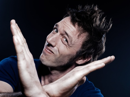 deny: studio portrait on black background of a funny expressive caucasian man time out pause gesturing