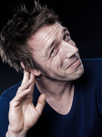 audition: studio portrait on black background of a funny expressive caucasian man with hearing problem Stock Photo
