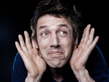 hesitancy: studio portrait on black background of a funny expressive caucasian man with hearing problem Stock Photo
