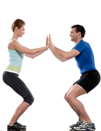 squats: one caucasian couple man aerobic trainer positioning woman  Workout coach Posture in indoors studio isolated on white background Stock Photo