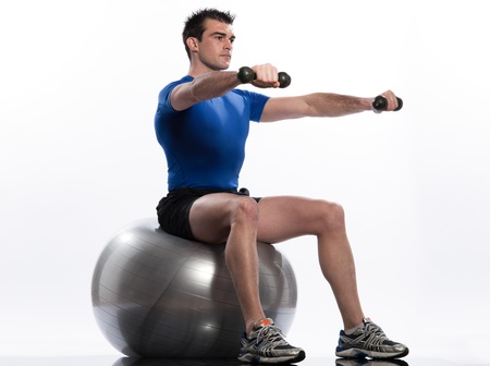 pilates man: one caucasian man exercising workout weigth training sitting on fitness swiss ball full length isolated on white background